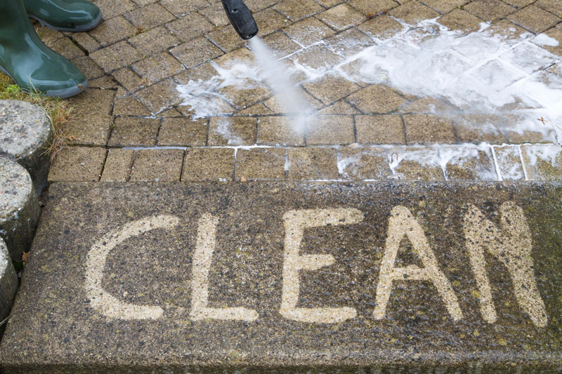 Pressure washer cleaning a path in front of the home; housekeeping services in Paducah KY